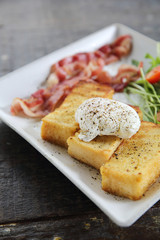 egg benedict with bacon on wood background , breakfast