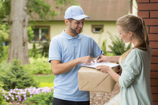 Courier holding a parcel and woman signing a delivery form