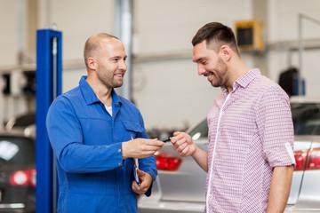 auto mechanic giving key to man at car shop