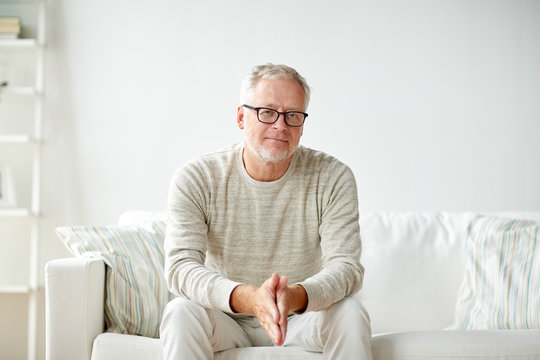 smiling senior man in glasses sitting on sofa