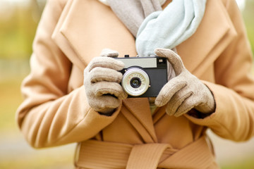 close up of woman with camera in autumn park