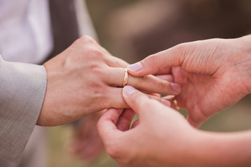 Closeup of a bride putting a gold wedding ring onto the groom's finger