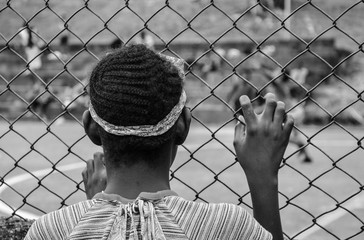 Girl looking to a soccer game through the fence