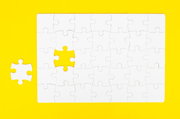 White, disassembled puzzle. On a yellow background.Top view. Flat lay.