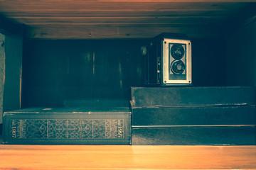 Vintage old camera over stack on books shelf. vintage filter