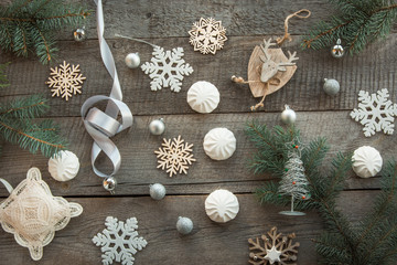 Christmas decor laid out on a wooden surface. Fir branches, silver ribbon and ball, white marshmallow, snowflakes, toy deer and decor around. Top view and copyspace. Flat lay. Shabby-chic
