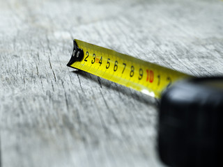 Self-retracting tape measure on wooden plank, focus on tape hook, closeup, shallow depth of field