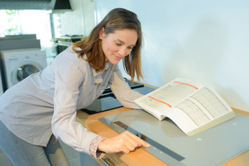 Woman holding instruction book and programming hob