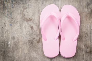 Flip-flops pink color on a wooden background.