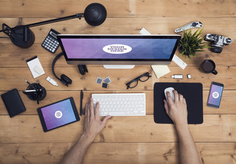 User with Desktop Computer, Tablet, and Smartphone on a Cluttered Wooden Table Mockup 1