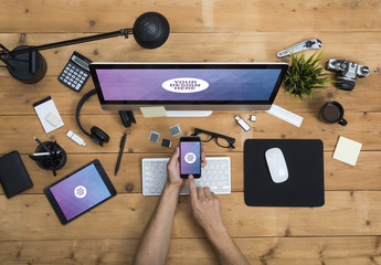 User with Desktop Computer, Tablet, and Smartphone on a Cluttered Wooden Table Mockup 2