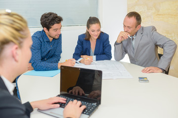 Three people in meeting, secretary using laptop