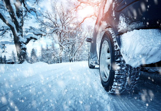 Car tires on winter road covered with snow. Vehicle on snowy alley in the morning at snowfall