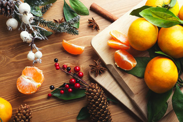 Top view of tangerines with leaves in Christmas decor.