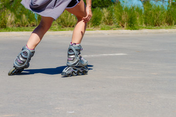 Close-up of female legs in roller skating on asphalt