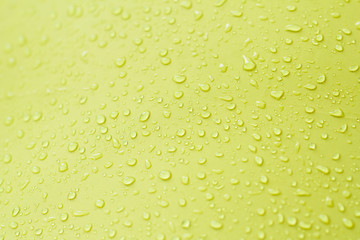 Drop of water on yellow background