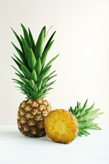 Ripe pineapples on a white wooden background