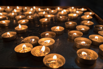 lit votive candles in church on black background