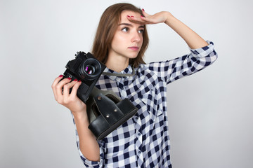 Portrait of a pretty woman  in plaid shirt holding an old camera in hands standing over gray background .and looks into the distance