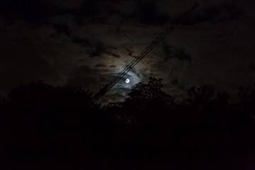 Mond über den Bäumen hinter den Wolken