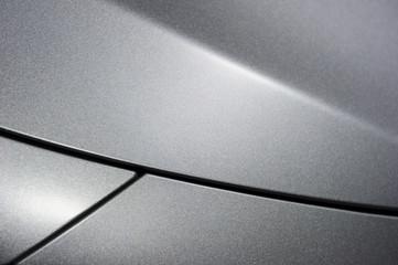 Surface of metallic sport sedan car, detail of metal hood and fender of vehicle bodywork