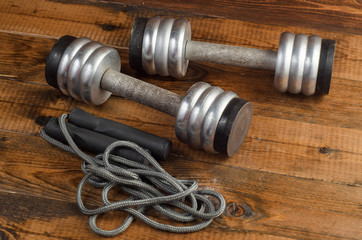 set with dumbbells and skipping rope on wooden background