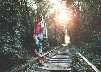 Young woman walking on the rails in the evening
