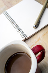 Blank page of a spiral notebook and coffee cup