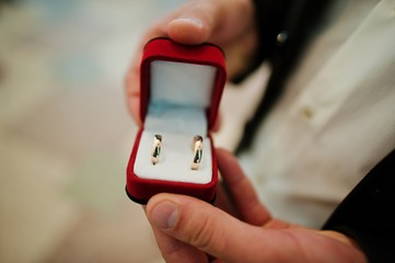 Marriage proposal. wedding rings at hand of groom in red velvet box