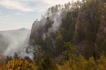 Rocks Aygira in forest fire smoke. Bashkortostan. Southern Urals