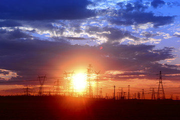 Many high voltage towers under the sunset