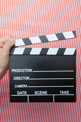 movie marker or clapper board set against a colorfull background