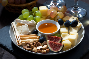 Plate with deli snacks and glasses of wine, closeup