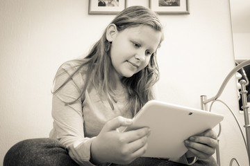 gril sitting and watching on her computer tablet