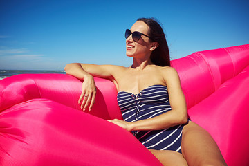 A lovely woman sitting on a pink inflatable boat on the beach