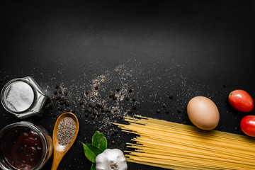 Food frame. Pasta ingredients - tomatoes, garlic,  herbs, salt, spaghetti pasta and egg on  black grunge background with copy space, Top view