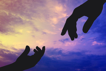 Silhouettes of father and child hands reaching to each other on sky background. Help and care concept.
