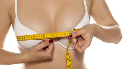 woman measures her breasts with a measuring tape