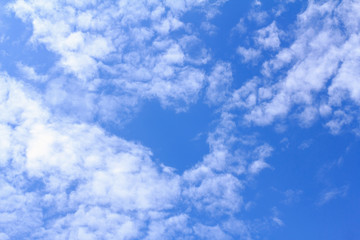 Blue sky background with white clouds. The vast blue sky and clouds sky on sunny day. White fluffy clouds in the blue sky.