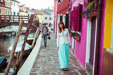 Girl in white jacket and mint dress walks along the pink house