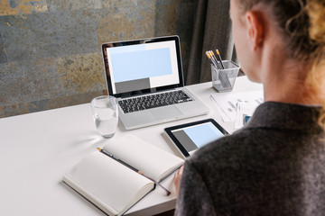 Back view. Business woman in gray shirt sits at white desk. On table is  laptop with blue screen,notebook,digital tablet,glass of water and  pencil holders.