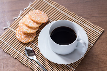 Black coffee in white cup and Crispy Rice Crackers with on woode