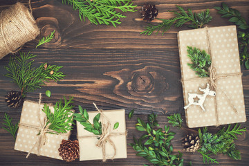 Christmas background with hand crafted gifts, presents  on rustic wooden table. Christmas or New year DIY packing. Holiday decor concept. Overhead, flat lay, top view, copy space