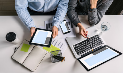 Top view of businessman and businesswoman sitting at white desk and do work together.Businesswoman showing pencil on laptop screen. Businessman using digital tablet.On table notebook,smartphone.