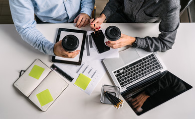 View from above.Businessman and business woman sitting at white desk,holding cups of coffee.Teamwork.On table laptop with black screen,smartphone,digital tablet,graphics,notebook, pencil holders.