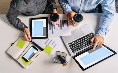 View from above.Business people sitting at white desk. Businessman pointing at laptop screen,holding in his other hand cup of coffee.Teamwork.On table smartphone,digital tablet, graphics, notebook.