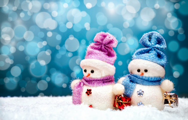 Cute snowmen couple with blue winter background