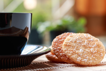 Crispy Rice Crackers with Hot cup of coffee on wooden table back