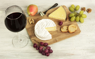 Red wine and selection of cheeses with grapes