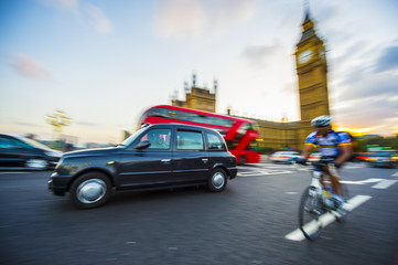 Traffic and cyclists share the road in motion blur on Westminster Bridge with a view of Big Ben and Westminster Palace